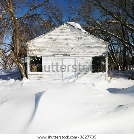 White house in snow covered landscape. - stock photo