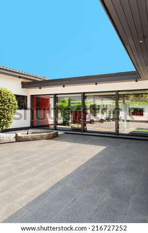 white house, outdoors, courtyard , glass wall - stock photo