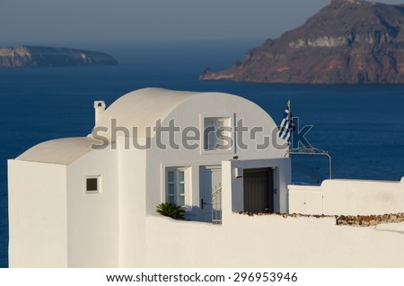 White House with the flag of Greece, stands on top of a cliff in the town of Oia on the Greek island of Santorini - stock photo
