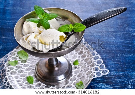 White ice cream with a mint leaf in metal ware. Selective focus
