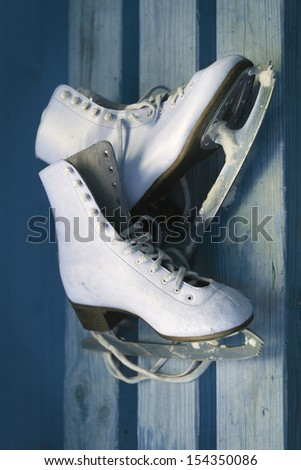 White ice skates on an old  wooden board - stock photo
