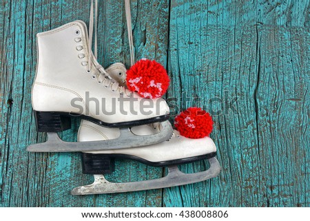 white ice skates with red yarn pompoms on turquoise painted wood