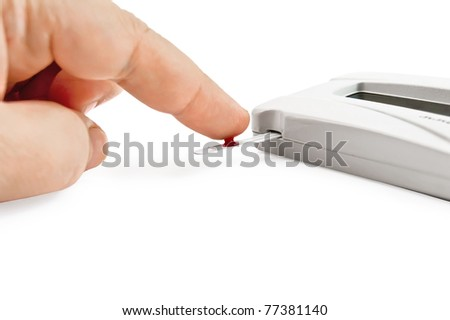 White instrument for measuring glucose levels with test strips, hand and drop of blood is isolated on a white background - stock photo