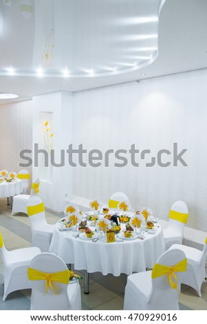 white interior of the restaurant. white interior with yellow napkins, sunny decor cafe. restaurant interior white and yellow