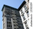 White Iron building in Manhattan, with fire escape - stock photo