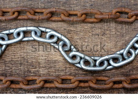 white iron chains forming waves and rusty chain on wooden texture background - stock photo