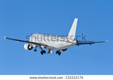 White jet airplane taking off, against blue sky - stock photo