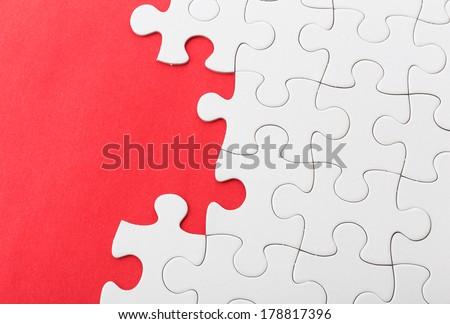 White jigsaw over red background - stock photo