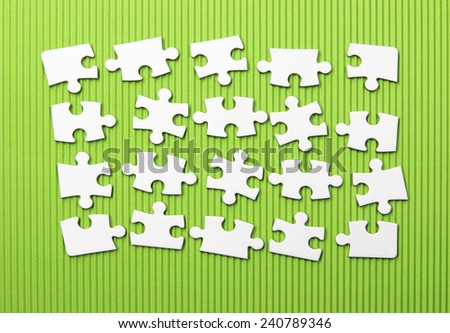 White jigsaw puzzle on green wave background  - stock photo