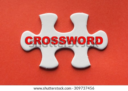 White jigsaw puzzle with a written word crossword on a red background. - stock photo