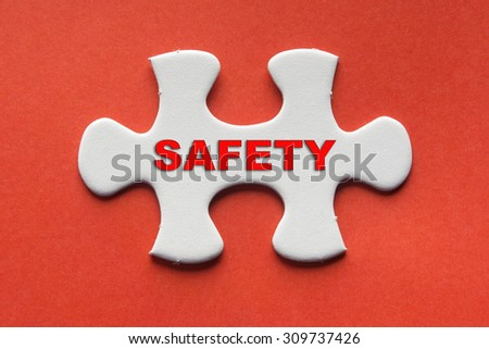 White jigsaw puzzle with a written word safety on a red background. - stock photo