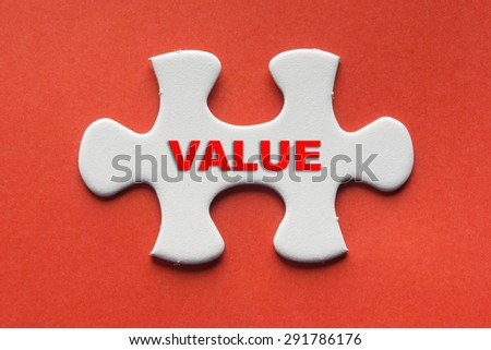 White jigsaw puzzle with a written word Value on a red background. - stock photo