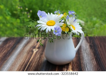White jug with bouquet of meadow flowers on wooden table and green grass - stock photo