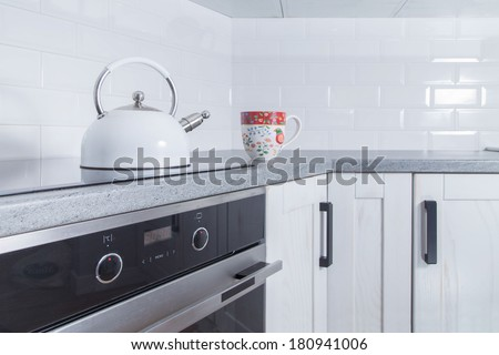 White kettle and colorful cup in modern rustic kitchen - stock photo