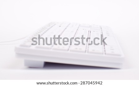 White keyboard with wire on isolated white background, side view - stock photo