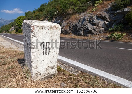 White kilometer stone post on the roadside in Montenegro - stock photo