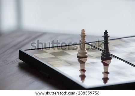 White king facing black king on chess board - stock photo
