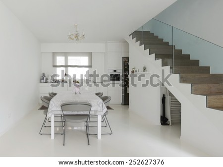 white kitchen and dining room with white epoxy floor - stock photo
