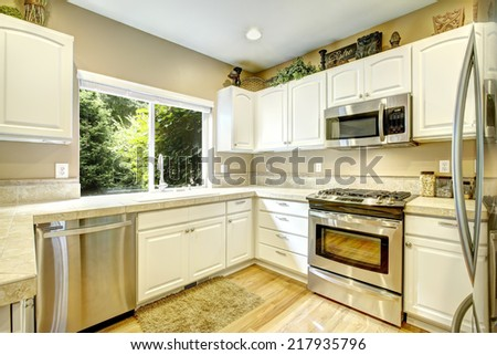 White kitchen cabinets with steel appliances and light tone hardwood floor - stock photo