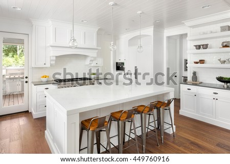 White Kitchen Interior with Island, Sink, Cabinets, and Hardwood Floors and Built In Shelving in New Luxury Home with Lights Off