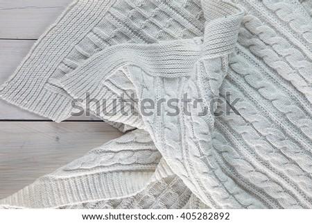 white knitted blanket. spit on the blanket. lying on white wooden floor in soft folds - stock photo