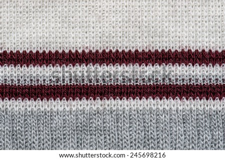 White knitting wool with red and gray stripes texture background. - stock photo