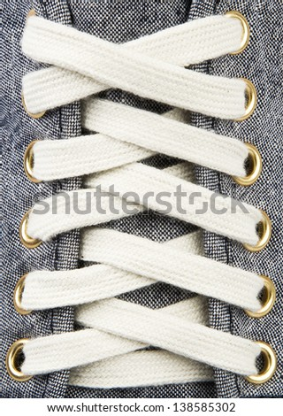 White lace on blue sneakers close up - stock photo