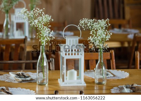 White lantern and glass bottles holding babys breath. Centerpieces for rustic barn wedding.