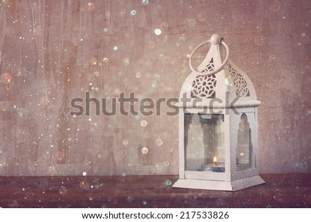 white lantern over wooden table and glitter lights background - stock photo
