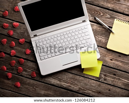 White laptop and hearts with sticky notes and notepad on old wooden table. - stock photo