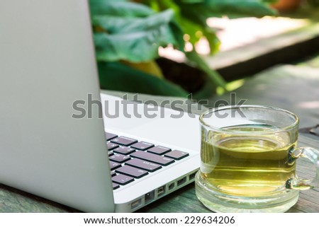 White laptop and tea cup business on wood table - stock photo