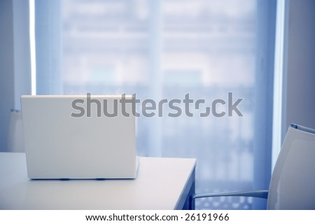 White laptop open on a white room, blue light coming from window - stock photo