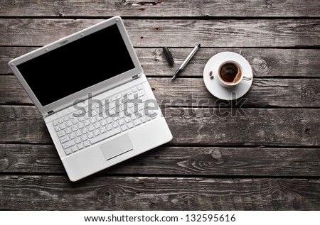 White laptop with coffee cup and pen on old wooden table. - stock photo