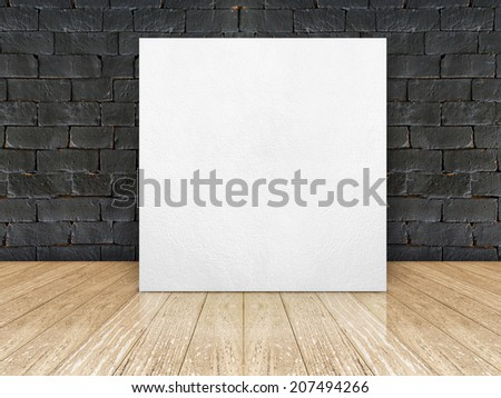 white leather frame at black brick wall and wooden plank floor