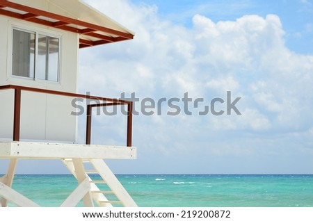 White Lifeguard house on a sandy beach in summer with turquoise ocean and blue cloudy sky  - stock photo
