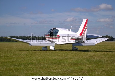 White light aircraft on a grass runway. - stock photo