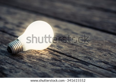 White light bulb glowing on the wood ground - stock photo