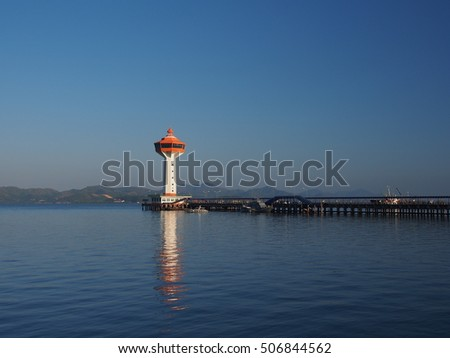 White light house with reflection in the ocean in day light vibe.