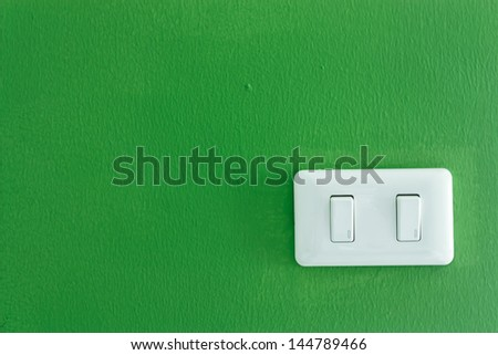 White light switch against a green wall - stock photo
