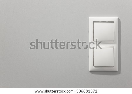 White light switches over a grey wall. Horizontal - stock photo