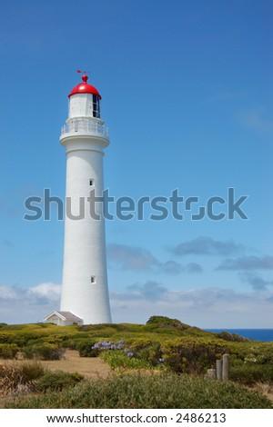White lighthouse against blue sky - stock photo