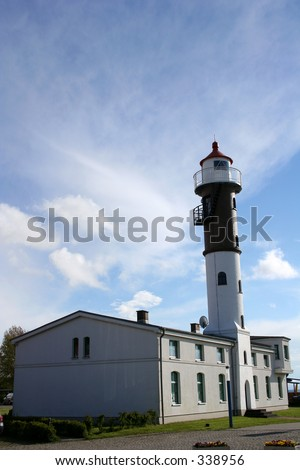 White lighthouse building against blue sky.
