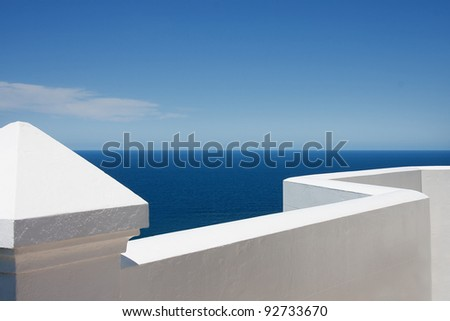 White lighthouse fence overlooking blue sea and sky - stock photo