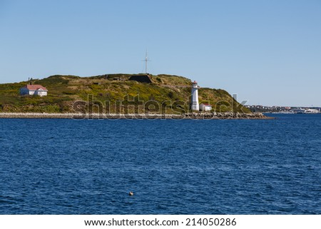 White Lighthouse on shore of green island near Halifax, Nova Scotia - stock photo