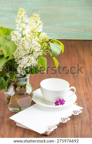 white lilac, lilac purple, white sheet of paper with hearts punching, punching with flowers on turquoise background, on a brown background, white porcelain cup - stock photo