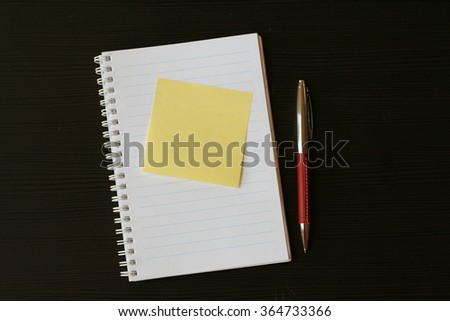 White lined scratchpad (notepad) with yellow post-it card and red pen on a black wooden table - stock photo