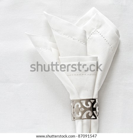 White linen napkin and silver napkin ring on as a table place setting - stock photo