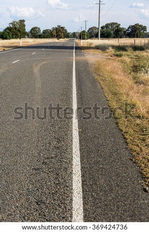 White lines along a road through dried crops in Australia.