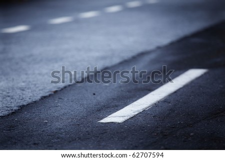 White lines on an old road. Shallow dept of field. - stock photo