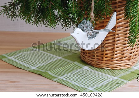 White little wooden bird with tin wings and fir branches in a wicker vase. Christmas-tree-toy bird